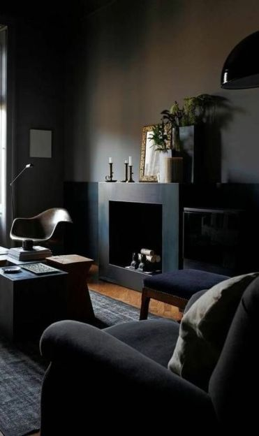 1-a-welcoming-dark-living-room-with-black-walls-a-fireplace-some-dark-upholstered-furniture-lamps-and-candles