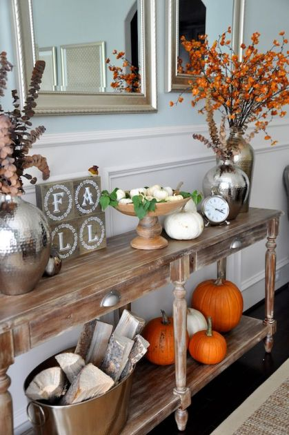 17-a-fall-console-with-orange-and-white-pumpkins-fall-leaves-and-dried-blooms-and-firewood-in-a-metal-bathtub