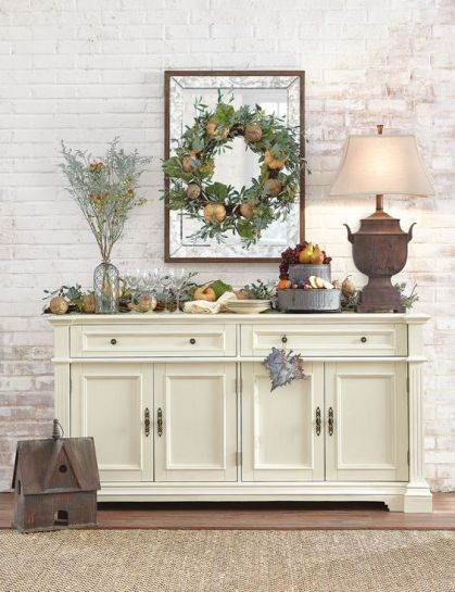 21-a-harvest-themed-console-table-with-faux-pumpkins-greenery-pinecones-faux-fruit-on-a-metal-stand
