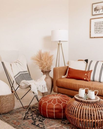 26-a-neutral-boho-space-with-a-tan-leather-sofa-and-a-rust-colored-ottoman-striped-textiles-pampas-grass-and-a-wooden-table