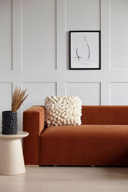 29-a-refined-modern-space-with-off-white-paneled-walls-a-terracotta-sofa-a-pompom-pillow-and-a-matching-vase