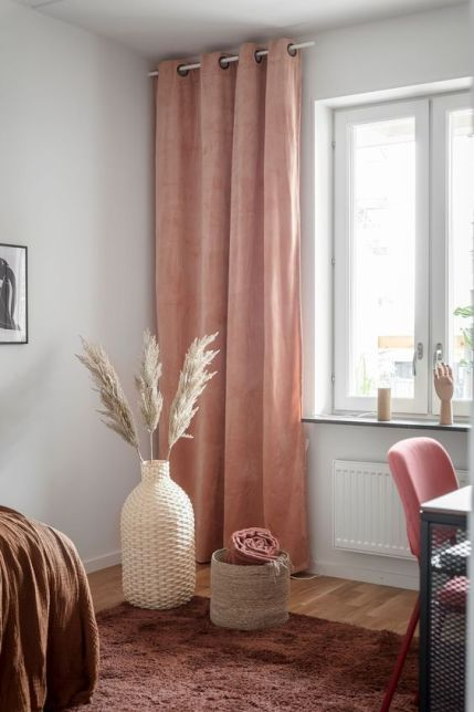 34-a-warm-colored-space-with-a-brown-rug-and-a-bedspread-a-pink-chair-and-rust-colored-curtains-that-add-warmth-here