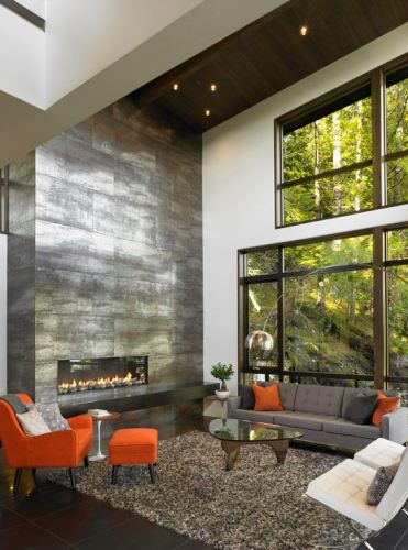 Stone-wall-fireplace-dark-wood-floor-shaggy-carpet-gray-orange-armchair