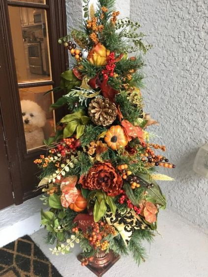 A-thanksgiving-tree-with-faux-blooms-pumpkins-fruits-berries-greenery-and-oversized-pinecones-is-very-lush