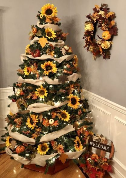 A-thanksgiving-tree-with-tan-ribbons-lights-sunflowers-leaves-and-pumpkins-topped-with-a-sunflower