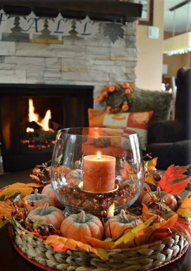A-basket-with-faux-pumpkins-and-berries-and-a-glass-with-a-candle-and-pebbles-for-the-fall