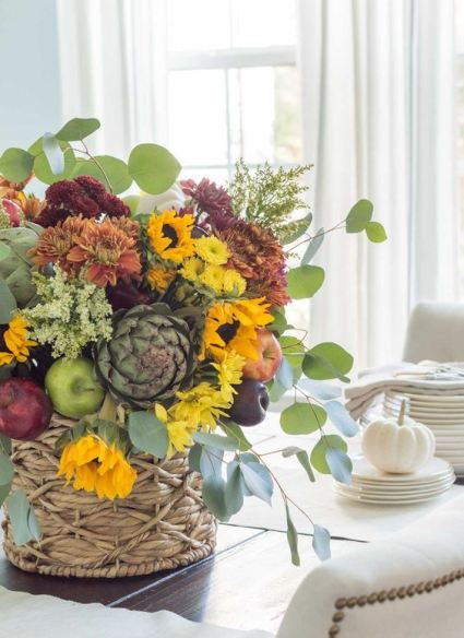 A-bold-fall-centerpiece-of-yellow-orange-and-rust-and-burgundy-blooms-greenery-faux-apples-and-pears-plus-foliage