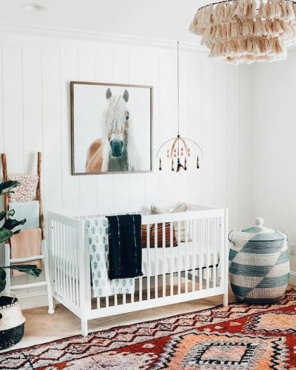 A-bright-boho-nursery-with-a-colorful-rug-a-printed-basket-with-a-lid-a-macrame-chandelier-colorful-textiles-and-a-horse-artwork