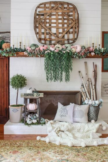 A-bright-fall-mantel-with-cascadign-greenery-pastel-pumpkins-greenery-branches-in-a-bucket-and-a-wooden-basket