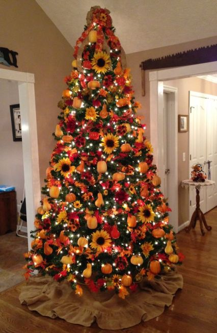 A-bright-fall-tree-with-lights-plaid-ribbons-faux-pumpkins-pears-sunflowers-and-a-red-bow-on-the-top