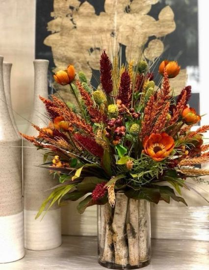 A-bright-rustic-arrangement-of-rust-burgundy-faux-blooms-dried-herbs-and-greenery-and-wooden-sticks-in-the-vase