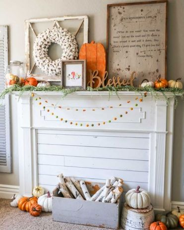 A-bright-rustic-flal-mantel-with-colorful-pompom-garlands-a-crate-with-birch-branches-lots-of-pumpkins-signs-and-a-cotton-wreath