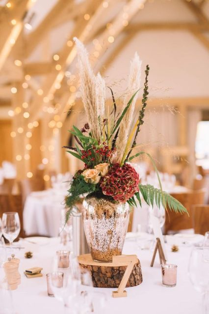 A-chic-wedding-centerpiece-of-a-mercury-glass-vase-and-rust-and-red-blooms-pampas-grass-and-ferns