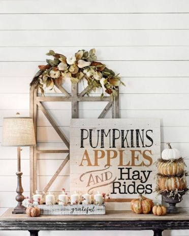 A-chic-whitewashed-wooden-sign-with-black-and-rust-colored-letters-pumpkins-and-candles-around