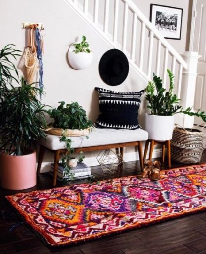 A-colorful-entryway-with-a-white-bench-a-colorful-boho-rug-potted-plants-a-black-printed-pillow-and-baskets-for-storage
