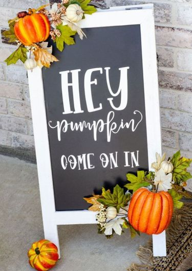 A-cool-black-and-white-fall-sign-decorated-with-faux-leaves-ad-pumpkins-is-a-cool-fall-decoration-for-outdoors