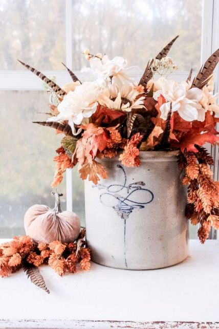 A-fantastic-fall-boho-centerpiece-of-white-blooms-fall-leaves-feathers-in-a-bucket-is-a-very-bold-and-chic-idea