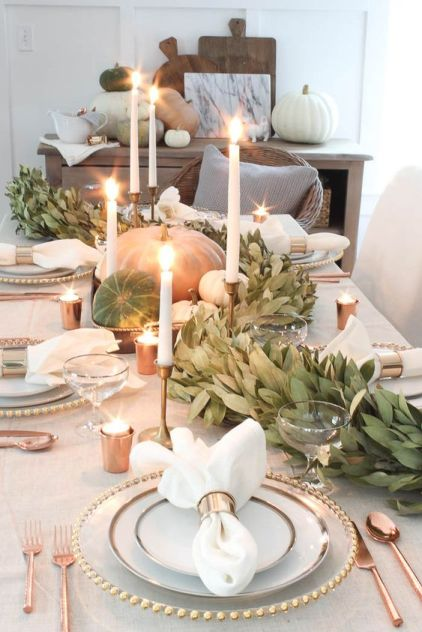A-gorgeous-fall-table-runner-of-greenery-natural-pumpkins-and-white-candles