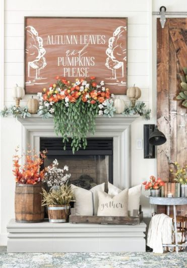 A-lush-fall-mantel-with-pale-greenery-faux-pumpkins-gorgeous-florals-and-cascading-greenery-fall-leaves-and-cotton-in-buckets-and-a-fall-sign