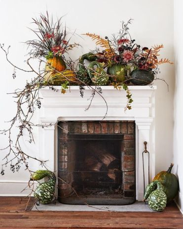 A-lush-harvest-mantel-decorated-with-greenery-long-branches-and-pumpkins-and-gourds-on-the-mantel
