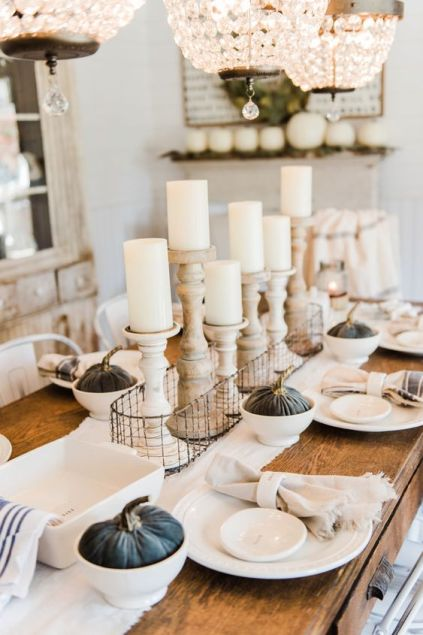 A-neutral-farmhouse-chic-tablescape-with-dark-fabric-pumpkins-wooden-candleholders-and-striped-napkins
