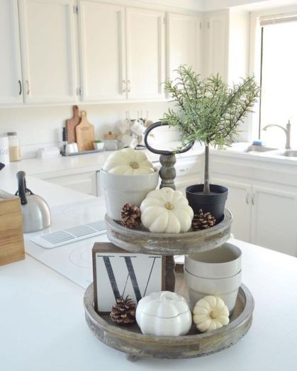 A-reclaimed-wooden-stand-with-white-and-porcelain-pumpkins-pinecones-a-potted-plant-and-a-letter-sign