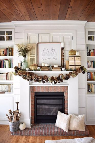 A-rustic-fall-mantel-with-a-pinecone-and-hydrangea-garland-white-pumpkins-and-faux-porcelain-ones-a-branch-arrangement-in-a-bucket