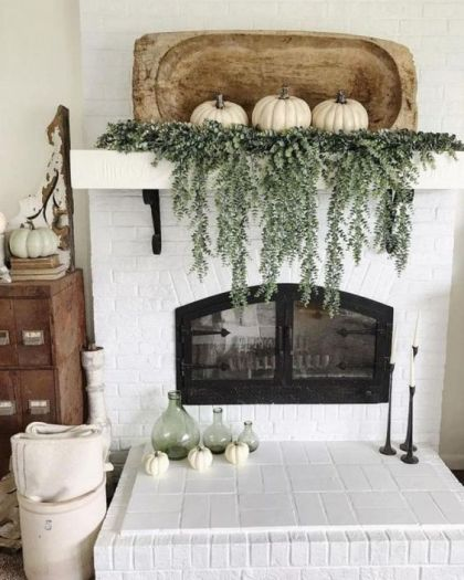A-rustic-fall-mantel-with-cascading-greenery-white-pumpkins-with-a-wooden-dough-bowl-plus-green-bottles