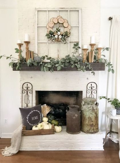 A-rustic-fall-mantel-with-greenery-candles-in-wooden-candleholders-a-crate-with-white-pumpkins-a-pillow-and-a-wood-slice-wreath
