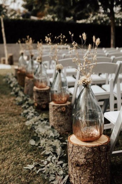 A-rustic-fall-wedding-arch-with-tree-stumps-vases-with-dried-grasses-and-blooms-and-eucalyptus