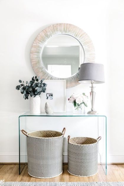 A-sheer-acrylic-console-a-couple-of-patterned-baskets-for-storage-a-wood-clad-mirror-and-a-chic-lamp