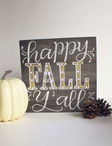 A-stained-wooden-sign-with-white-and-gold-letters-is-a-chic-and-cute-mantel-decoration-for-the-fall