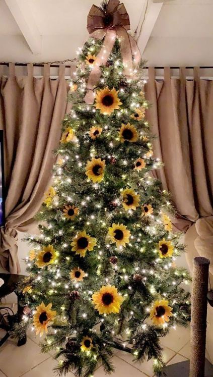 A-sunflower-thanksgiving-tree-with-lights-pinecones-blooms-and-a-large-taupe-bow-on-top
