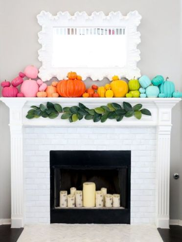 A-super-colorful-fall-mantel-with-super-bright-pumpkins-and-birch-inspried-candles-in-the-fireplace
