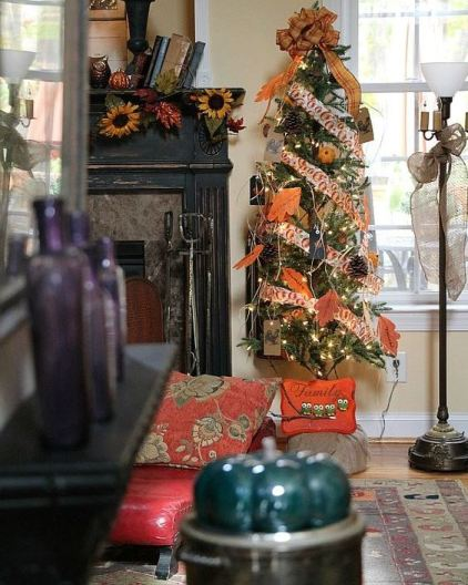 A-thankful-tree-with-bright-printed-ribbons-faux-leaves-pinecones-twine-lights-and-a-large-plaid-bow-on-top