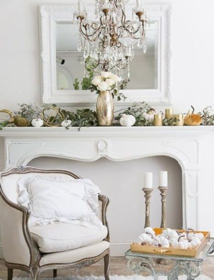 An-elegant-fall-mantel-decorated-with-fresh-greenery-fabric-and-porcelain-pumpkins-and-white-roses-in-a-metallic-vase