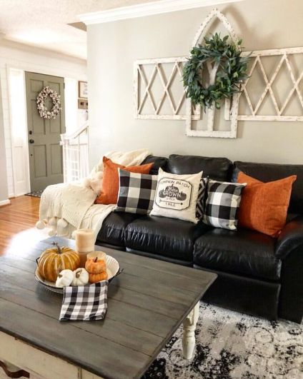 Bright-orange-pillows-and-a-bowl-with-pumpkins-and-candles-are-added-for-a-fall-touch-2