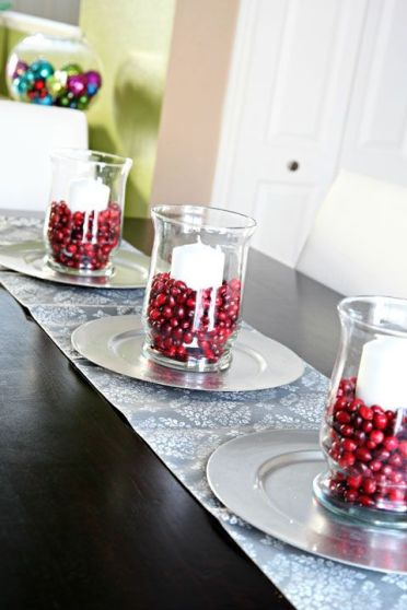 Glass-vases-with-pillar-candles-and-cranberries-for-decorating-the-table-for-the-fall