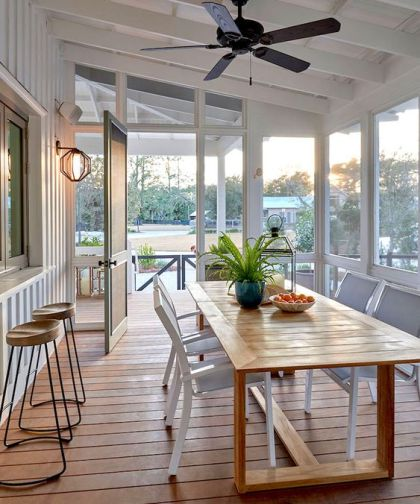 1-a-coastal-screened-porch-with-a-pass-by-window-a-wooden-dining-table-and-white-chairs-plus-views-of-the-surroundings