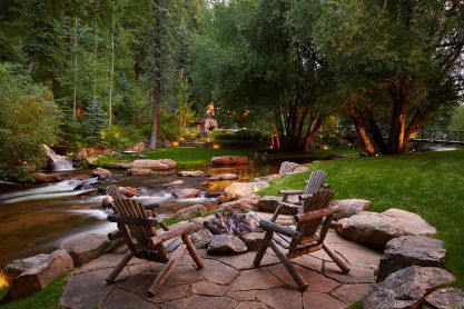 Expansive-and-relaxing-rustic-backyard-with-stone-deck-amazing-natural-water-feature-and-a-cozy-fireplace-64460