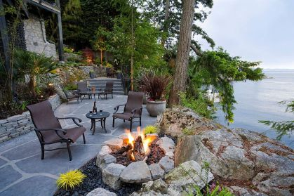 Rustic-waterside-terrace-and-backyard-with-fireplace-and-ample-sitting-space-35383