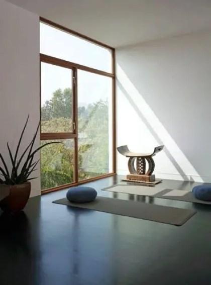 Ein-minimalistischer-Meditationsraum-mit-einem-großen-Fenster-für-Ansichten-und-einigen-Matten-und-Kissen
