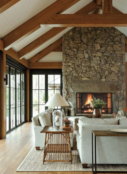 A-modern-farmhouse-living-room-with-a-gorgeous-fireplace-clad-with-stone-neutral-furniture-a-wooden-table-and-a-console-wooden-beams