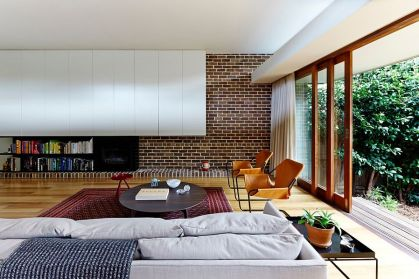 Modern-living-room-mixes-brick-wall-with-contemporary-shelves-in-white