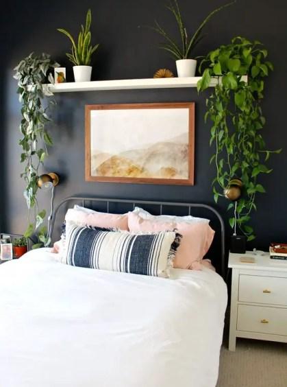 Ein-Boho-Schlafzimmer-mit-einer-schwarzen-Akzentwand-ein-Metallbett-und-ein-offenes-Regal-mit-Kletterpflanzen