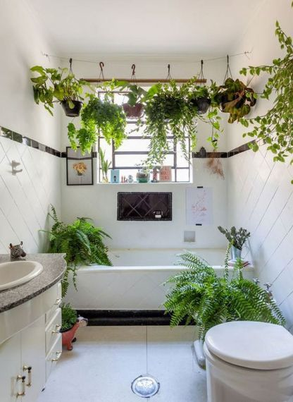 Ein-boho-weißes-badezimmer-in-schwarz-weiß-mit-kletterpflanzen-über-der-wanne-und-farnen-herum-fühlt-entspannt