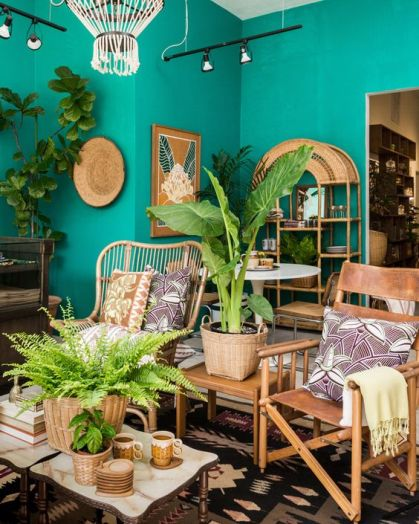 A-colorful-tropical-living-room-with-emerald-walls-rattan-and-leather-furniture-a-gold-mirror-potted-plants-and-bold-artworks