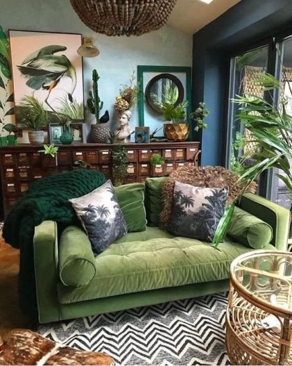 A-moody-tropical-living-space-with-blue-walls-a-vintage-sideboard-a-green-sofa-a-printed-rug-and-bold-artworks