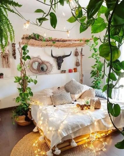 Ein-neutrales-Boho-Schlafzimmer-mit-vielen-Kletterpflanzen-Lichtern-und-Boho-Kissen-plus-Spiegeln