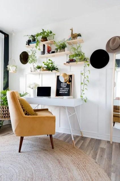 Ein-neutrales-Boho-Home-Office-mit-einem-kleinen-Schreibtisch-einem-gelben-Stuhl-und-offenen-Regalen-mit-Kletterpflanzen-in-Töpfen
